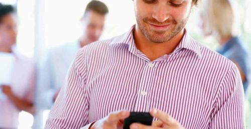 Мужчина смотрит на телефон и улыбается