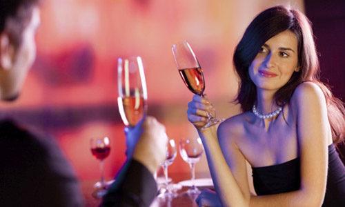 Женщина с бокалом вина смотрит на мужчину