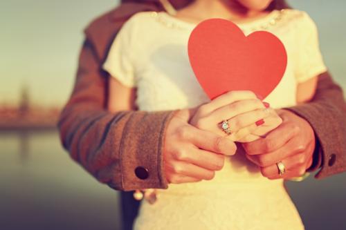 Мужчина обнимает женщину, женщина держит в руках сердце
